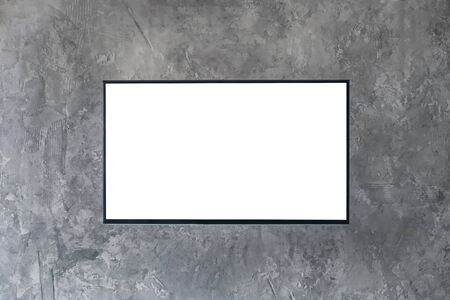 Mock up, copyspace, template, entertainment and technology concept - black flat smart led TV mockup with white blank screen hanging on grey grunge wall Banco de Imagens