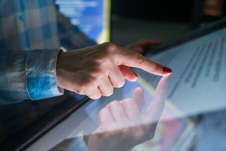 Education, entertainment, learning and technology concept - woman using interactive touchscreen display of electronic kiosk at modern museum or exhibition Stock Photo