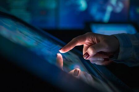Femme utilisant un écran tactile interactif d'un kiosque multimédia électronique dans un musée ou une exposition moderne. Concept d'éducation, d'apprentissage et de technologie