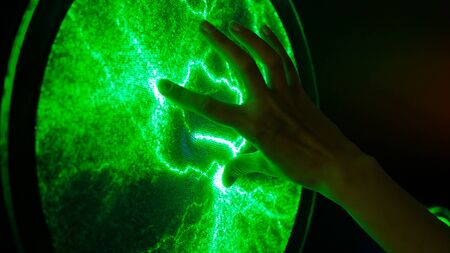 Interactive exposition in science museum. Woman touching plasma panel display. Electricity and physics concept Banco de Imagens