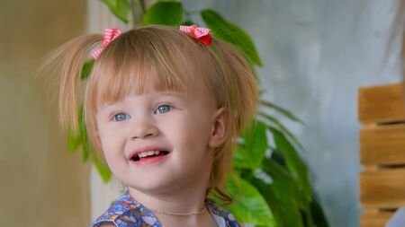 Portrait of funny shy little girl at home. Family, childhood and leisure concept