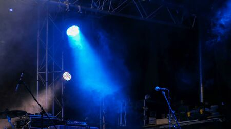 Free stage with blue lights before concert, lighting devices, microphone Stock Photo