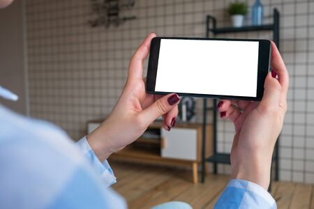 Over shoulder view: woman hands holding black smartphone with white blank screen in home interior. Mock up, copyspace, template, entertainment and technology concept