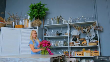 Professional woman floral artist, florist in blue dress holding and checking beautiful wedding bouquet at workshop, flower shop. Floristry, handmade and small business concept