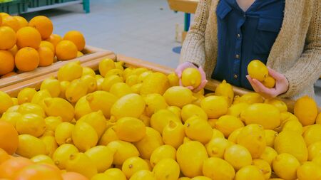 Woman buying fresh citrus fruits - yellow lemons at supermarket. Consumerism, sale, organic and health care concept Imagens