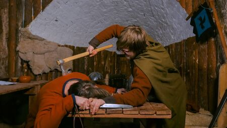 Murder, criminal, kill and medieval concept - murderer with axe - man in russian ethnic suit killing his opponent in tavern