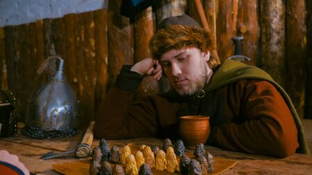 Portrait of pensive man in russian ethnic suit playing board game like chess. Folk, competition and traditional concept