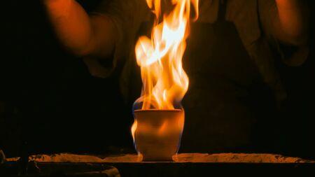 Tazza in ceramica ardente sul tornio in ceramica in officina, studio. Fatto a mano, arte e concetto di artigianato Archivio Fotografico