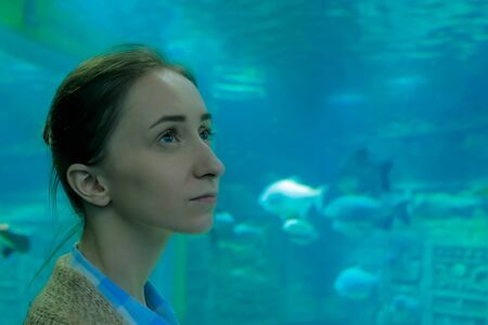 Underwater life, tourism, education and entertainment concept. Portrait of woman looking at fish in large public aquarium tank at Oceanarium Stock fotó