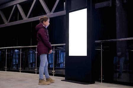 Femme regardant un kiosque d'affichage blanc interactif vierge vertical lors d'une exposition ou d'un musée avec un intérieur de science-fiction futuriste. Maquette, fond, modèle, isolé, écran blanc, concept technologique
