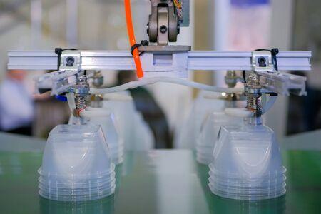Pila di contenitori per alimenti in polipropilene sul nastro trasportatore della macchina per lo stampaggio a iniezione di plastica automatica con braccio robotico in mostra, fiera commerciale. Produzione, industria, concetto di tecnologia automatizzata Archivio Fotografico