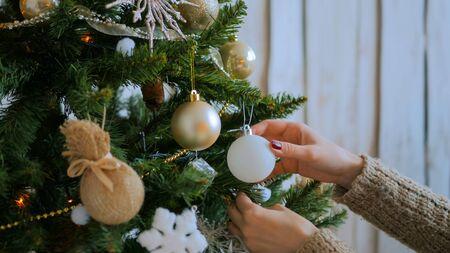 Woman decorating christmas tree with toys. Holidays, x-mas and christmas concept