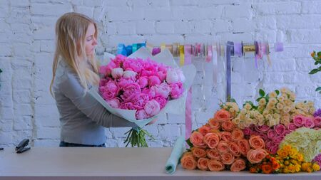 Professional woman floral artist, florist holding pink peonies bouquet at workshop, flower shop. Floristry, handmade and small business concept