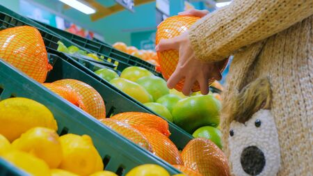 Woman buying fresh exotic citrus fruits - sweetie, sweety, pomelo at supermarket. Close up shot of woman hands. Consumerism, sale, organic and health care concept Stok Fotoğraf