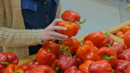 Woman buying vegetables - fresh red bell peppers at supermarket. Close up shot of woman hands. Consumerism, sale, organic and health care concept