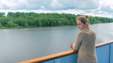Young woman standing on deck of cruise ship and looking at river and landscape. Relax, nature and journey concept 스톡 콘텐츠