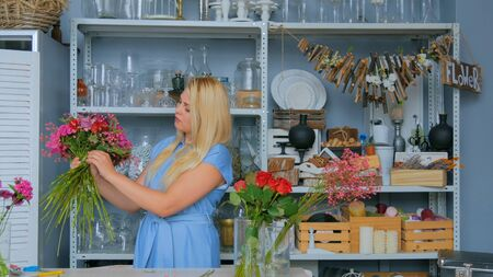 Professional woman floral artist, florist in blue dress making beautiful wedding bouquet at workshop, flower shop. Floristry, handmade and small business concept Imagens