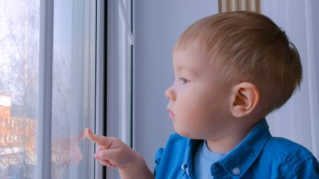 Pensive little boy looking through window. Childhood and leisure concept