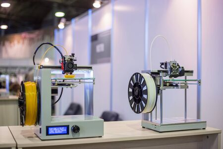 Two automatic 3D printers during work at modern technology exhibition. 3D printing, additive technologies, 4.0 industrial revolution and futuristic concept