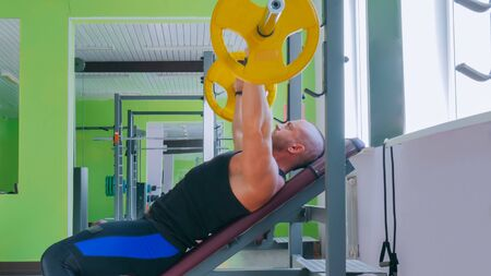 Athletic young man doing exercises with barbell at gym, fitness club. Bodybuilding, lifestyle and sport concept