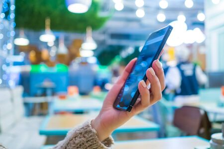 Woman hand using smartphone in cafe - scrolling and touching. Blurry bokeh background. Technology and entertainment concept