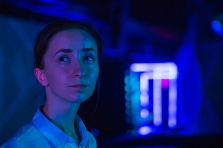 Retrato de rostro de mujer mirando a su alrededor en la exposición inmersiva moderna con poca iluminación. Fondo borroso bokeh. Concepto de educación, arte digital y entretenimiento.
