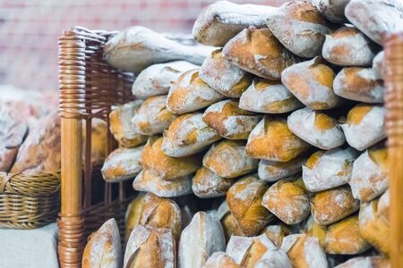 Assortment of freshly baked baguette breads for sale on counter of shop, market or bakery. Pastry, breakfast, food and traditional french cuisine concept