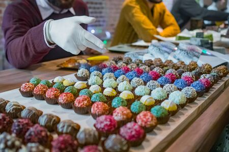 Assortment of colorful delicious fresh truffle cakes for sale on counter of shop, grocery, market, cafe or bakery. Dessert, sweet food and confectionery concept
