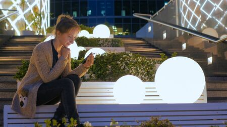 Woman using smartphone in the city - scrolling and touching. Evening time, twilight. Relax, entertainment and technology concept
