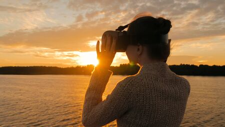 Woman using virtual reality headset on deck of cruise ship at sunset. Sunset light, golden hour, sun lens flares. Relax, future and technology concept