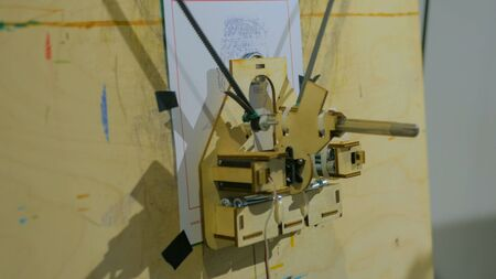 Robotic arm with pen drawing portrait at technology robotic exhibition. Future and art concept