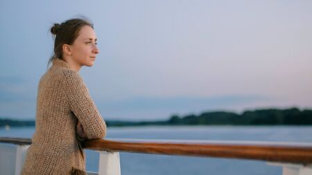 Woman standing on deck of cruise ship and looking at landscape after sunset. Relax, nature and journey concept