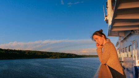 Woman standing on deck of cruise ship and looking at landscape. Sunset light, golden hour. Nature and journey concept