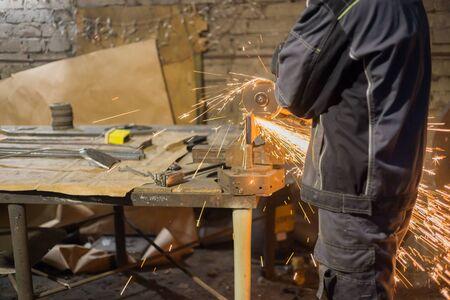 Professional blacksmith sawing metal with hand circular saw at forge, workshop. Handmade, craftsmanship and blacksmithing concept Archivio Fotografico
