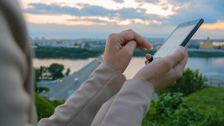 Woman using smartphone in the city after sunset - scrolling and touching. Evening time, twilight. Relax, entertainment and technology concept