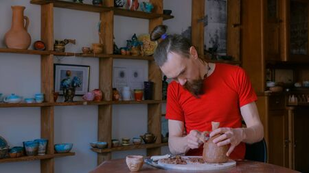 Professional male potter shaping and scraping dry clay jar with special tool in pottery workshop, studio. Crafting, artwork and handmade concept