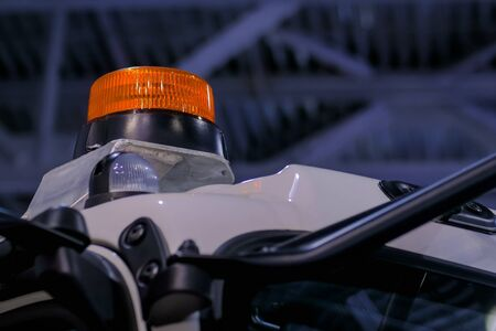 Close up of warning orange beacon flashing on roof of emergency, support and service vehicle. Danger, legal, alert light, attention and hazard concept