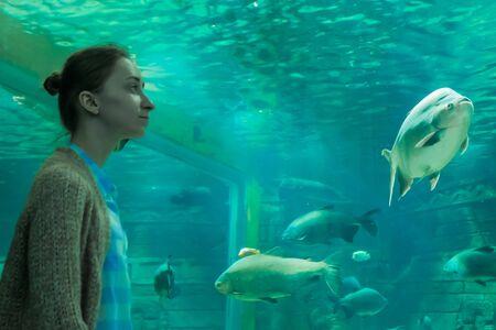 Underwater life, tourism, education and entertainment concept. Portrait of woman looking at fish vortex in large public aquarium tank at oceanarium