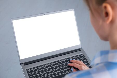 Mockup image: woman typing on laptop computer keyboard with white blank screen in home or office. Mock up, copyspace, freelance workspace, template, entertainment and technology concept