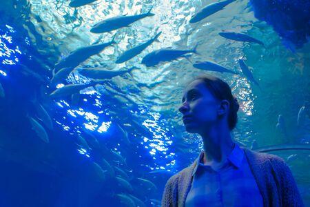 Portrait of woman looking at fish vortex in large public aquarium tank at oceanarium. Tourism, education, underwater life and entertainment concept Stock fotó