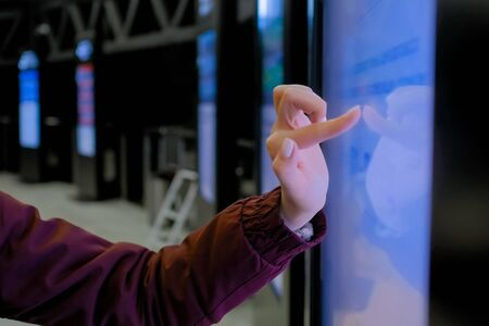 Woman hand using interactive touchscreen display of electronic multimedia kiosk at modern museum or exhibition - scrolling and touching - close up view. Education, futuristic and technology concept Reklamní fotografie