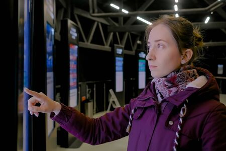 Portrait of woman using interactive touchscreen display of electronic multimedia black kiosk with public transport schedule at bus or train station with low light illumination, scrolling and touching