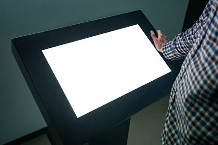 Man looking at white blank interactive touchscreen display of electronic multimedia kiosk in dark room of technology exhibition - close up view. Mock up, copyspace, template and futuristic concept Stock Photo