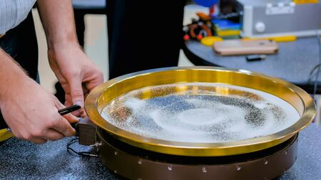 Sound vibration transforms white sand particles on steel surface at technology futuristic exhibition. Science, resonance and physics concept Stock fotó