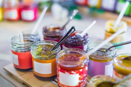 Delicious colorful jam, jelly or confiture in little glass jar with white blank label on counter of shop, market, cafe - close up view. Dessert, mock up, sweet food and confectionery concept