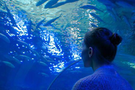 Underwater life, tourism, education and entertainment concept. Portrait of woman looking at fish vortex in large public aquarium tank at oceanarium with blue low light illumination Stock fotó