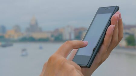 Woman using smartphone on embankment - close up shot - scrolling and touching. Technology concept