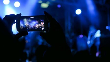 Unrecognizable hand silhouette taking photo or recording video of live music concert with smartphone. Photography, entertainment and technology concept