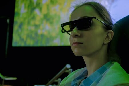 Portrait of woman face with 3d glasses looking around in movie theater with shaking seat, panoramic screen and low light illumination. Technology, 3d movie, entertainment, leisure time, cinema concept Reklamní fotografie