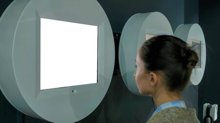 White screen, mock up, future, copyspace, template, isolated, technology concept. Woman looking at blank digital interactive white display wall at exhibition, museum with futuristic sci-fi interior